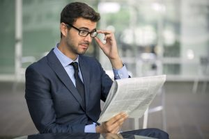 Shocked businessman with glasses reading newspaper