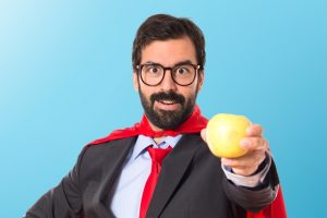 Hipster businessman dressed like superhero holding an apple