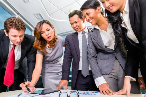 Businesspeople standing around a table